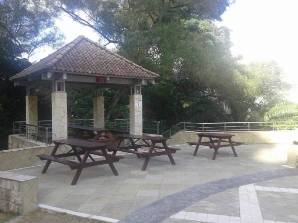 A pavilion with tables and a barbeque pit. Беседка со столиками и мангалом для барбекю.